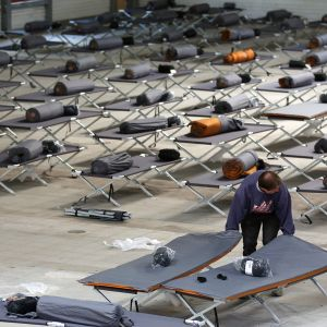 Tuolloin uuden vastaanottokeskuksen työntekijä valmisteli turvapaikanhakijoiden majoitusta Hampurissa 18. syyskuuta 2015.