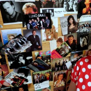 Nuori nainen katselee artistien fanipostikortteja seinällä
