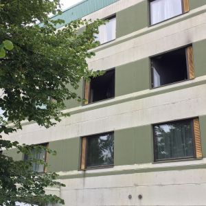 Kaksi mustaa ikkuna-aukkoa elementtikerrostalossa