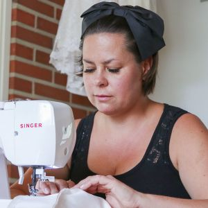 Maria Perätalo ompelee vauvan mekkoa.