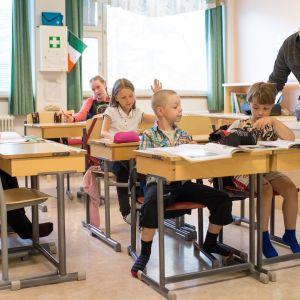 Kuvassa opettaja neuvoo oppilaita luokassa