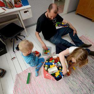 Isä leikkii Legoilla lasten kanssa.