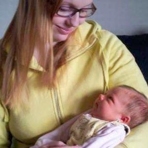 Silmälasipäisellä naisella on vauva sylissään käärittynä kapaloihin