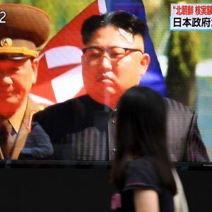 Tokiolaiset kulkivat televisioruudun ohi sunnuntaina, jossa Pohjois-Korean johtaja Kim Jong-un esiintyi.