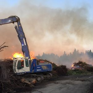 Kaivuri pöyhii risukasaa tulipalopaikalla