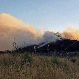Isosta risukasasta nousee savua, kun kaksi palomiestä samuttaa tulipaloa vesiruiskuin.