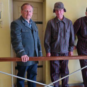 Kaksi miestä pukeutuneina vangeiksi ja yksi vartijaksi