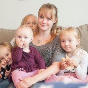 Äiti lasten kanssa sohvalla.
