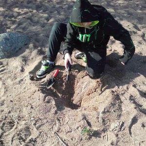 Poika etsii hiekasta aarteita