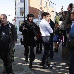 Poliisi ja useita siviilejä kadulla.