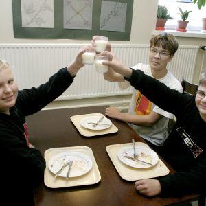 Kolme poikaa skoolaa maitolaseilla.