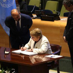 Valkotakkinen nainen kirjoittaa kynällä valkoiseen paperiin