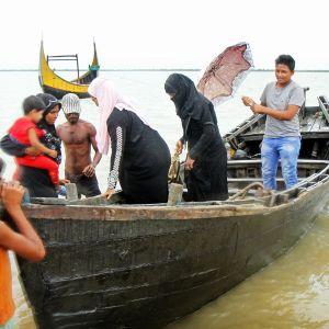 Rohingya-pakolaisia rantautumalla veneellä.