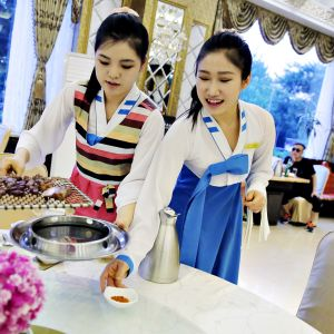 Kaksi perinteiseen korealaiseen mekkoon pukeutunutta nuorta tyttöä kattaa pöytää.