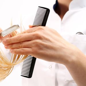 nainen leikkaa hiuksia