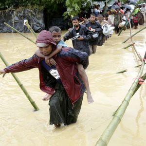 Rohingyapakolaisia ylittämässä jokea.