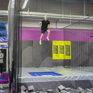 Poika hyppää trampoliinilla.