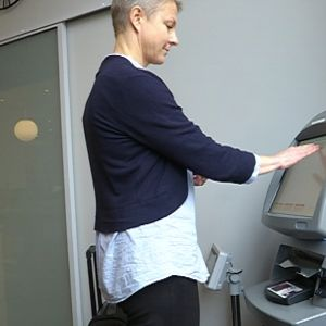Nainen käyttää nurkassa seisovaa automaattia