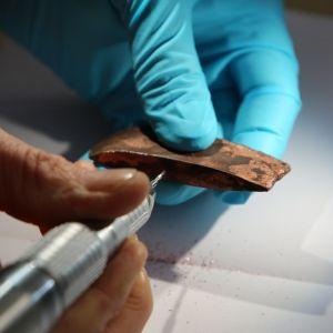 Pieni kuparikirveen terä tutkijan hansikoidussa kädessä. Hän tutkii materiaalia kynämäisellä instrumentilla.