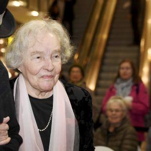 Eeva Kilpi vastaanottaa Nummisuutarin Eskon käsipuolessa  Suomalaisen Kirjallisuuden Seuran (SKS) Aleksis Kiven rahaston palkinnon.