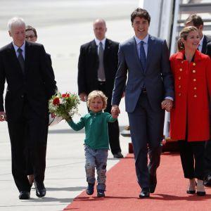 Justin ja Sophie Trudeau sekä heidän poikansa Hadrian kävelevät punaista mattoa pitkin lentokentällä.