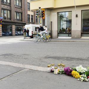 Kukkia ja muistokynttilöitä Annankadun ja Lönnrotinkadun risteyksessä Helsingissä lauantaina 29. heinäkuuta
