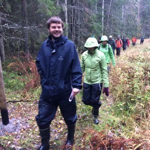 Ihmisiä kulkee jonossa metsäaukealla.