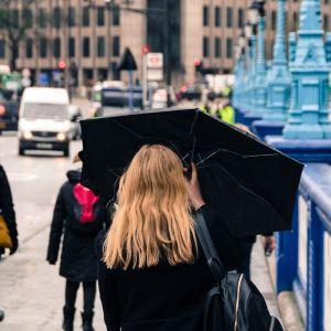 Nainen kadulla sateenvarjon alla Lontoossa.