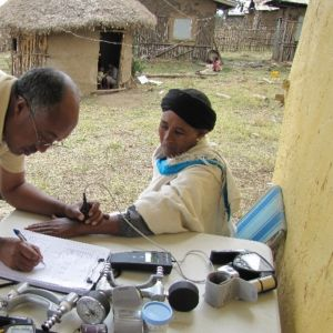 Pihalla pöydän ääressä seisova tutkija pitää mittaria istuvan koehenkilön ranteen päällä ja kirjoittaa ylös lukemaa.