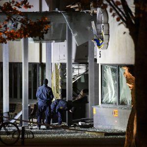 Poliisin rikospaikkatutkijat ja hajonnut poliisiaseman sisäänkäynti.
