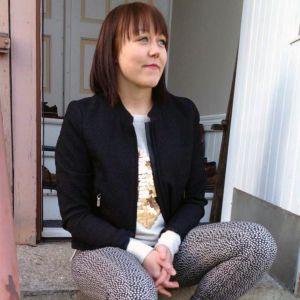 Saara hanhela istuu kotitalonsa portailla