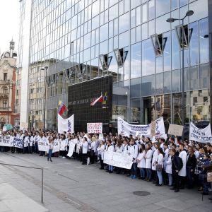 Mielenosoittajia kylttien kanssa lasisen rakennuksen edessä.