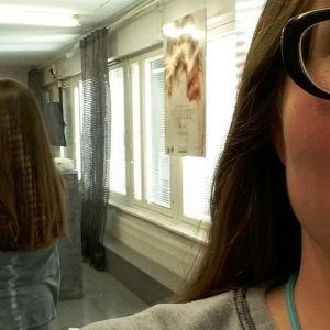 Nainen kuvaa hiuksia peilin kautta