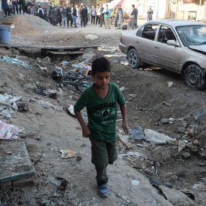 Kabulilaispoika kuvattuna kadulla, vieressä tuhoutunut auto ja taustalla ihmisiä.