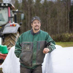 Ari Korhonen nojaamassa viljapaaleihin.