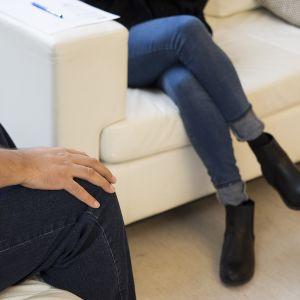 Mies ja nainen istuvat erillisillä sohvilla.