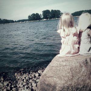 kaksi tyttöä istuu selin kameraan kivellä