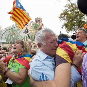 Itkevä barcelonalainen halaa toista.