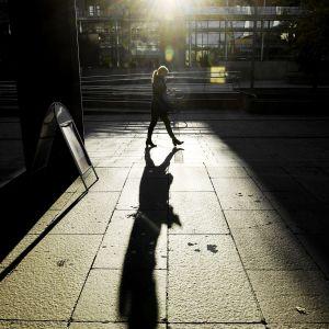 Nainen kävelee aurinkoisessa Kampissa helsingissä.