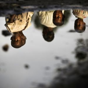 Kongolaiset lapset heijastuvat maassa olevasta vedestä.