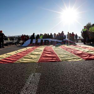 Mielenosoittajia Katalonian lipun kanssa tiesululla.