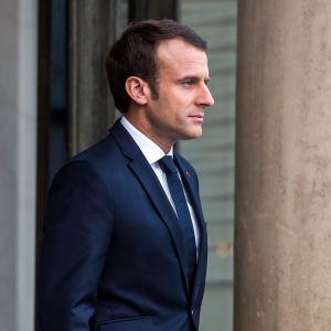Ranskan presidentti Emmanuel Macron seisoo pylvään vierellä.