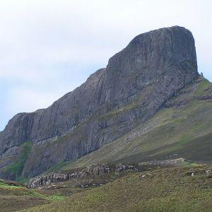 Kumpuilevaa turvamaastoa, jonka keskellä nousee jyrkkä vuori.