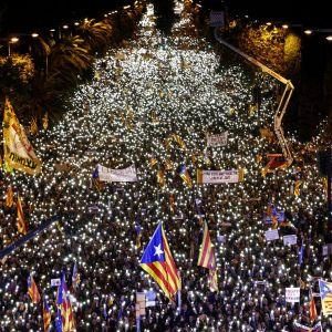 Mielenosoittajia kadulla, käsissä valaisevat matkapuhelimet.