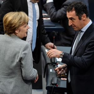 Merkel ja Özdemir puhuvat toisilleen ilmeet vakavina.