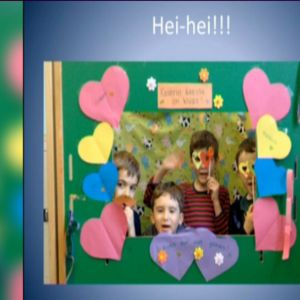 Neljä lasta vihreässä pahvi-ikkunassa, jonka reunoille on askarreltu pahvisia sydämiä.