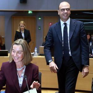 Mogherini istuu hymyillen etualalla vasemmalla.
