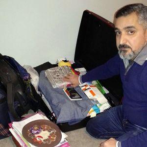 Mies pakattujen laukkujen äärellä