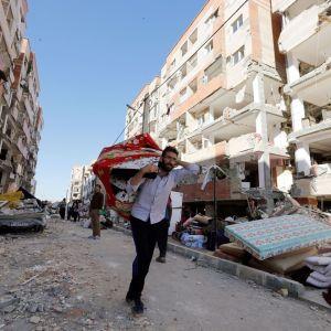 Parrakas silmälasipäinen mies kantaa kankaaseen käärittyä kantamusta maanjäristyksen koettelemalla kadulla. Taustalla näkyy toinen mies, joka tarkastelee järistyksen vaurioittamia kerrostaloja. Kadulla on järistyksen levittelemää rakennusromua. Taivas on pilvetön, aurinko valaisee kadun toista puolta.