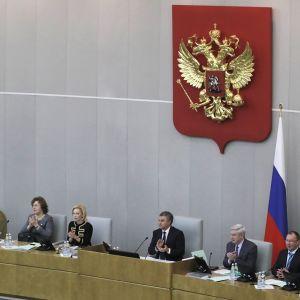 Seitsemän kansanedustajaa taputtaa duuman salissa, puhemiehen korokkeen takana. Keskellä istuu duuman puhemies Vjatšeslav Volodin tummassa puvussa. Vaalealla seinällä on suuri Venäjä vaakuna, kullattu kaksipäinen kotka punaisella pohjalla.